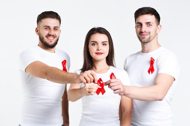 Groep vrienden met waterverf van rood lint. de dagconcept van aids van de wereld. op de witte achtergrond Premium Foto