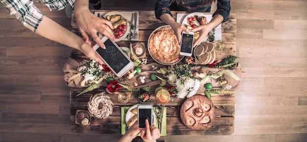 Groep vrienden nemen een foto met mobiele telefoon voor de lunch. bovenaanzicht. Gratis Foto