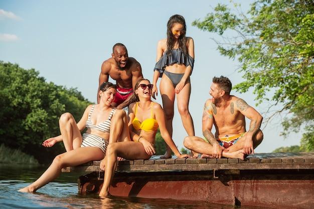 Groep vrienden opspattend water en laughting op de pier op de rivier Gratis Foto