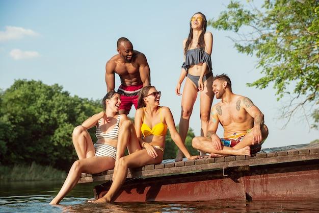 Groep vrienden opspattend water en laughting op pier op rivier Gratis Foto
