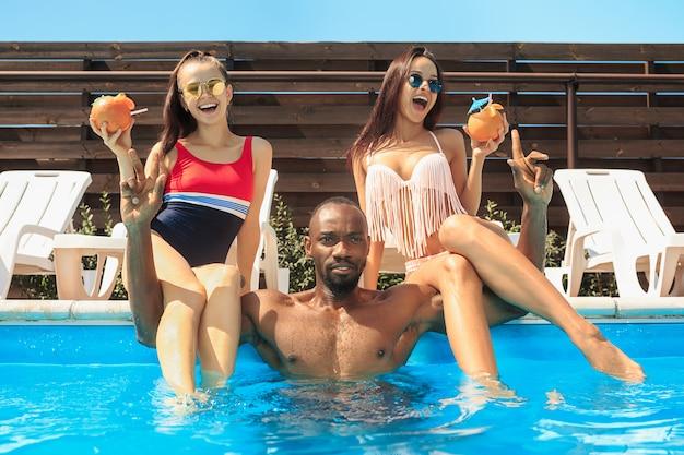 Groep vrienden spelen en ontspannen in een zwembad tijdens de zomervakantie Gratis Foto