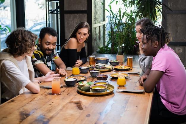 Groep vrienden zitten en eten in een café Premium Foto