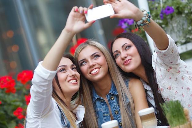 Groep vriendinnen maken van een selfie foto op de mobiele camera glimlachen. mooie vrouwen plezier in het café. jonge meisjes lachen Premium Foto