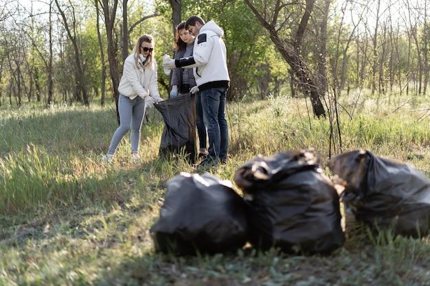 Groep vrijwilligers reinigt het park van puin. drie mensen in het voorjaar verzamelen plastic afval. milieuvervuiling concept Premium Foto