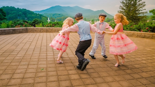 Groep vrolijke kinderen die samen spelen en dansen in een gebied omgeven door prachtig groen Gratis Foto