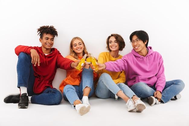 Groep vrolijke tieners geïsoleerd, roosteren met koolzuurhoudende dranken Premium Foto