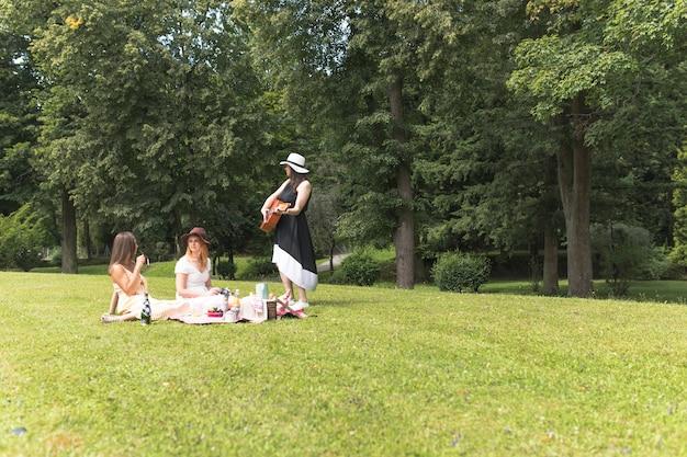 Groep vrouwelijke vrienden die op de picknick in het park genieten van Gratis Foto