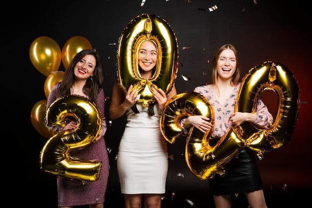 Groep vrouwen bij de holdingsballons van de nieuwjarenpartij Gratis Foto
