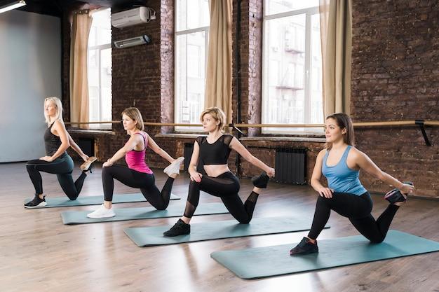 Groep vrouwen die samen bij de gymnastiek opleiden Gratis Foto