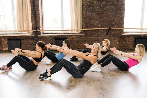 Groep vrouwen die samen bij de gymnastiek uitwerken Gratis Foto