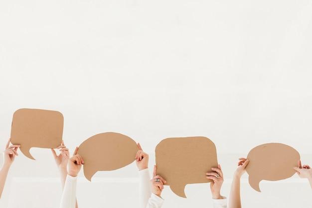 Groep vrouwenhanden die praatjebellen houden Gratis Foto