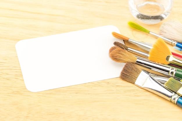 Groep waterverfborstel en lege witboekkaart op houten lijst Premium Foto