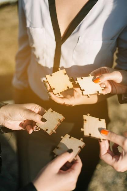 Groep zakenlui die houten puzzel houden Gratis Foto