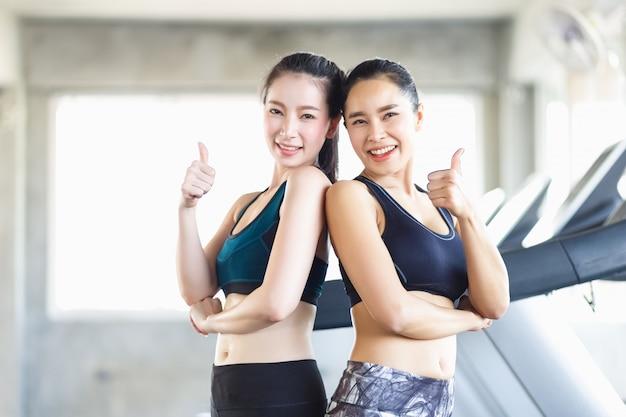 Groeps aantrekkelijke aziatische vrouw die de spieren uitrekken en na oefening, training, geschiktheid bij gymnastiekclub ontspannen. sport recreatie blij lachend meisje is genieten met haar trainingsproces. Premium Foto