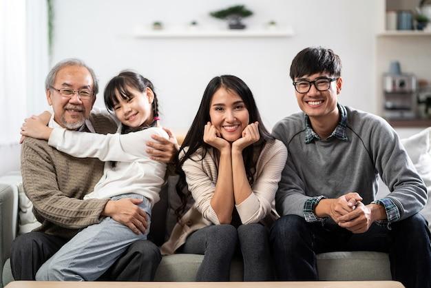 Groepsportret van aziatische en gelukkige familie zittend op de banklaag in de woonkamer met een glimlach Premium Foto