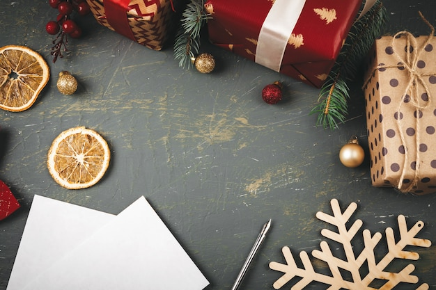 Groetbrief, envelop en veer omringd door kerstversiering Premium Foto