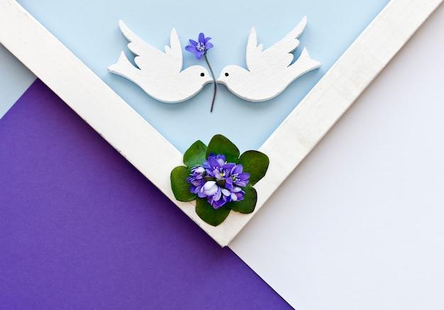 Groetkaart met blauwe bloemen en twee witte duiven op de kleurrijke document achtergrond. Premium Foto