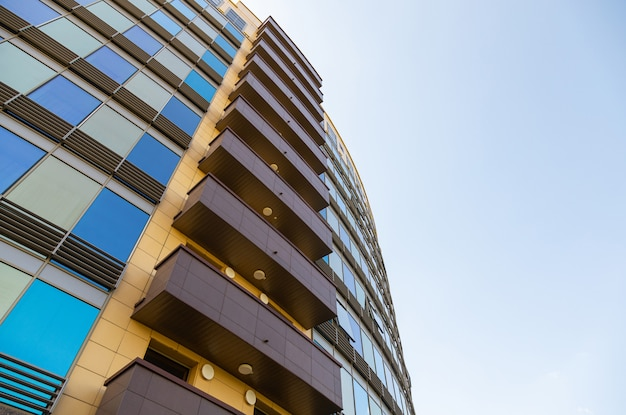 Grondmening van blauwe en gouden glasoppervlakte van de bouw van muur met vensters en bruine balkons Premium Foto