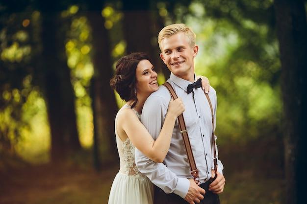 Groom omhelst zachtjes haar bruidegom in het bos Gratis Foto