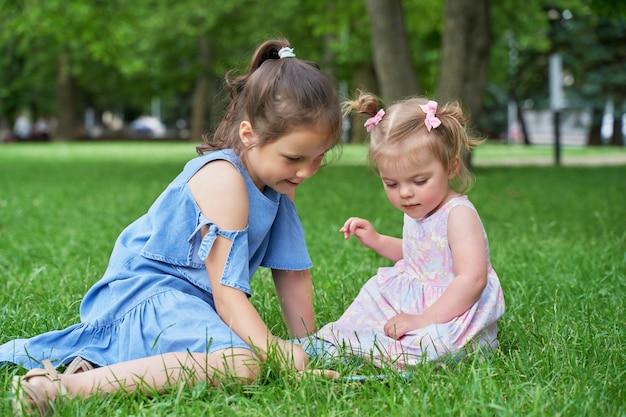 Groot meisje en een klein meisje zitten op het groene gras en kijken naar de telefoon Premium Foto