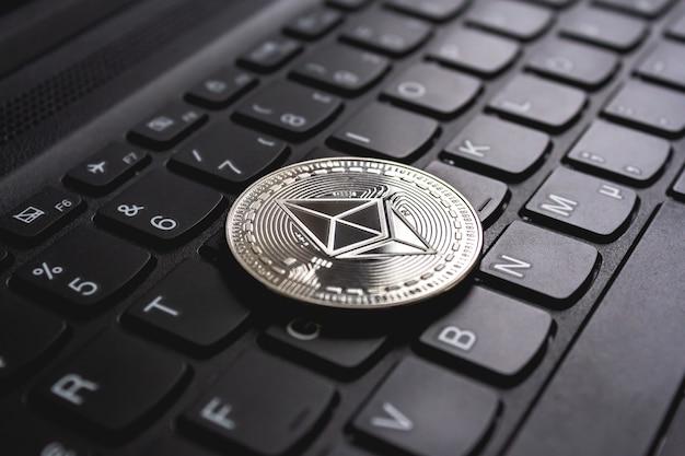 Groot muntstuk dat bovenop een zwart computertoetsenbord wordt geplaatst Gratis Foto