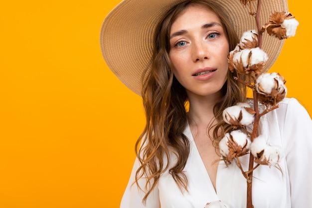 Groot portret van een mysterieus meisje van middelbare leeftijd in een hoed op een sinaasappel, houdt zachtjes natuurlijk katoen in haar handen Premium Foto