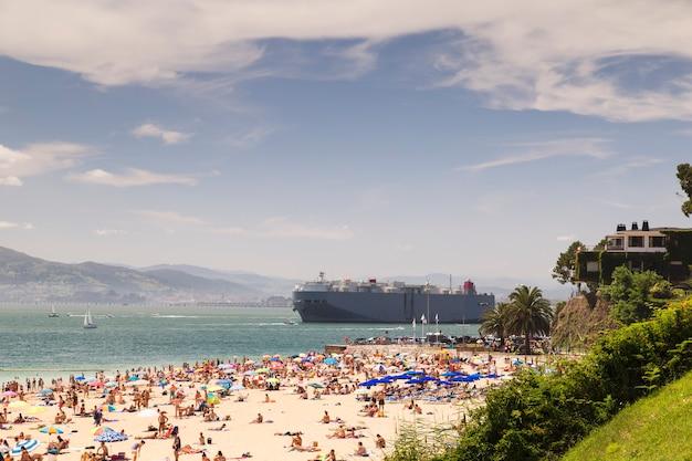Groot schip in de buurt van dichtbevolkt strand Premium Foto