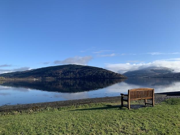 Groothoek opname van een houten bankje op een groen veld voor water en een berg Gratis Foto