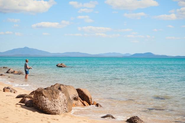Groothoek opname van een man die vissen op het strand onder een heldere blauwe hemel Gratis Foto