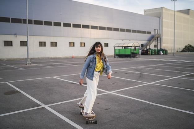 Groothoek opname van een meisje op een skateboard achter een gebouw Gratis Foto