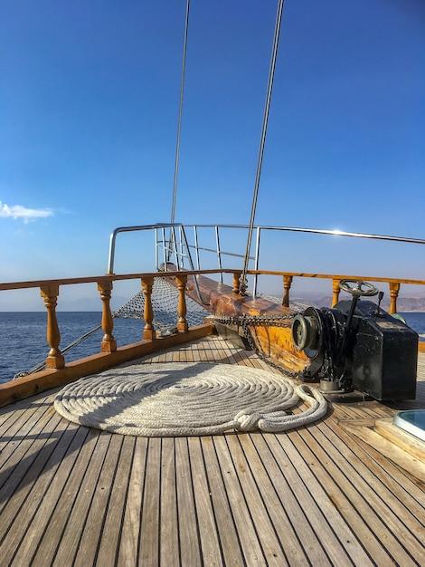 Groothoek opname van een touw gedraaid in een cirkelvormige positie op een schip boven de oceaan onder een blauwe lucht Gratis Foto