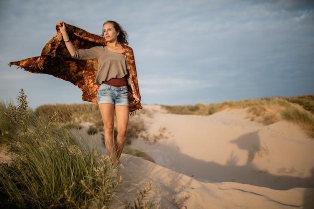 Groothoek opname van een vrouw die overdag op het zand loopt Gratis Foto
