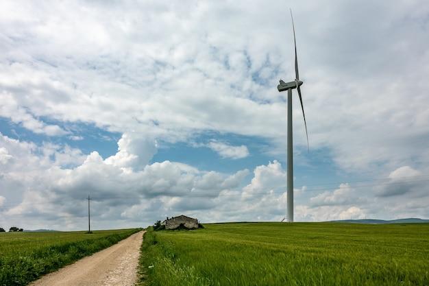 Groothoek opname van een windventilator naast een groen veld onder een bewolkte hemel Gratis Foto
