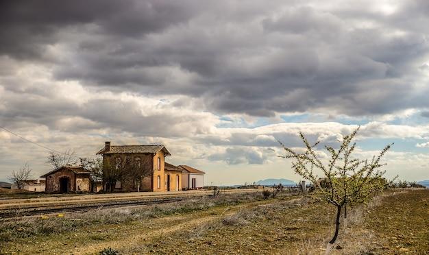 Groothoek opname van oude huizen op een groen veld onder een bewolkte hemel Gratis Foto