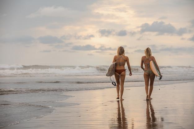 Groothoek opname van twee meisjes met surfplanken wandelen op het strand Gratis Foto