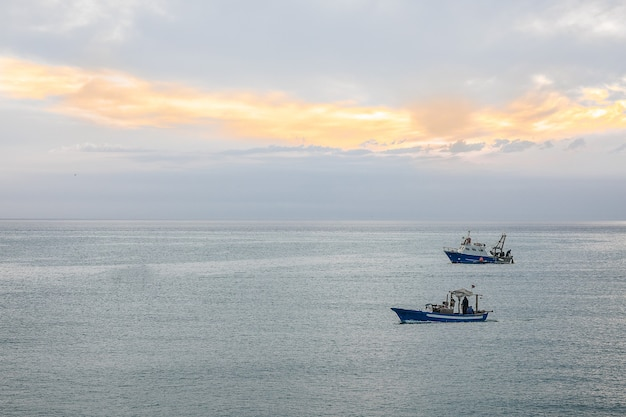 Groothoek opname van twee schepen die onder een bewolkte hemel over de oceaan varen Gratis Foto