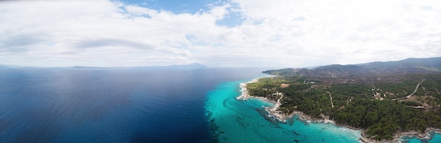 Groothoekopname van de rotsachtige kust van de egeïsche zee met, groen rondom, struiken en bomen, heuvels en bergen, blauw water met golven, uitzicht vanaf de drone griekenland Gratis Foto