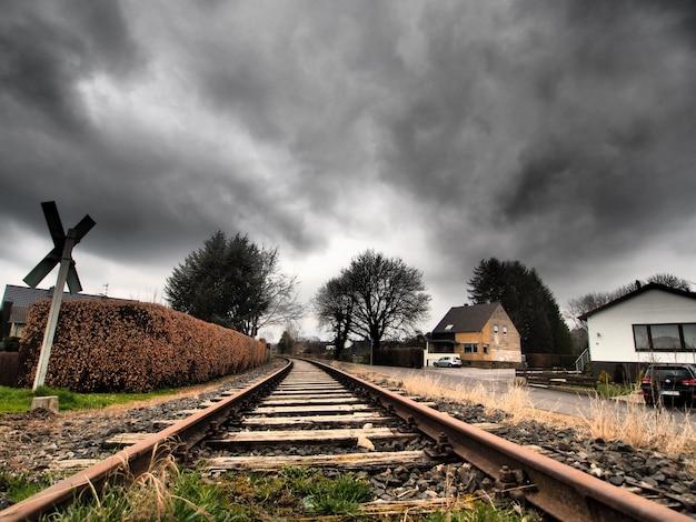 Groothoekopname van de spoorlijnen omgeven door bomen onder een bewolkte hemel Gratis Foto