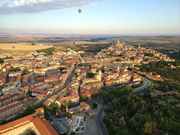 Groothoekopname van veel gebouwen omringd door bomen en een parachute in de lucht Gratis Foto