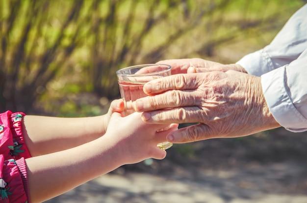 Grootmoeder die een glas schoon water geeft aan een kind. selectieve aandacht. Premium Foto