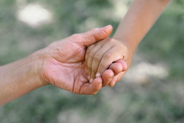 Grootmoeder en kind houden elkaars hand vast Premium Foto