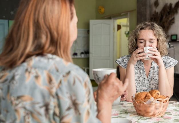Grootmoeder en kleindochter drinken koffie tijdens het ontbijt Gratis Foto