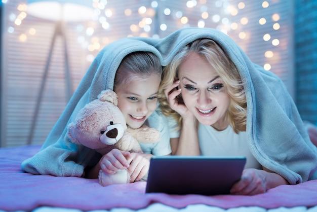 Grootmoeder en kleindochter kijken film op tablet. Premium Foto