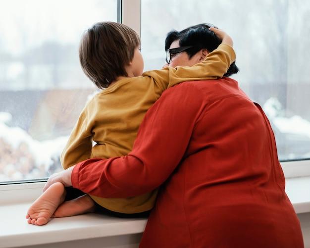 Grootmoeder en kleinzoon kijken samen door het raam Gratis Foto