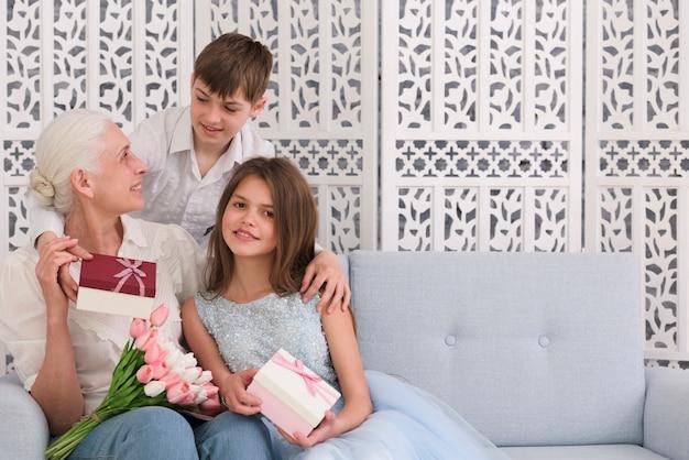 Grootmoeder met haar kleinkinderen die giftdoos en bloemboeket houden Gratis Foto