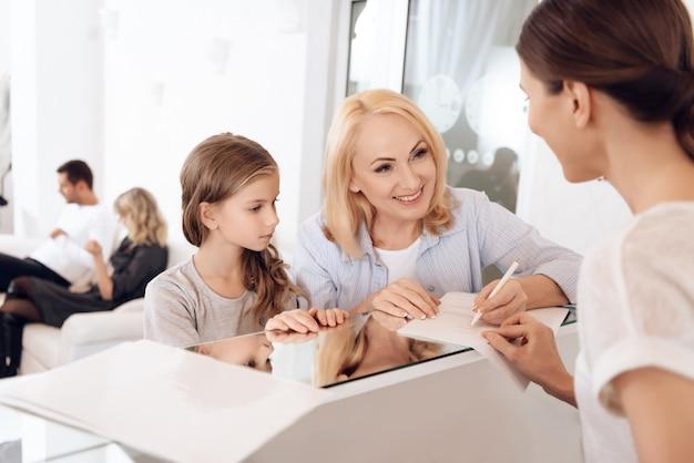 Grootmoeder met kleindochter vult documenten in. Premium Foto