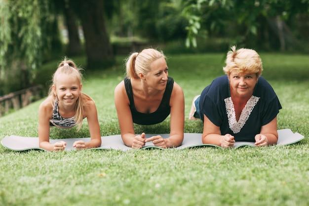 Grootmoeder, moeder en kind doen samen fitness in de natuur Premium Foto