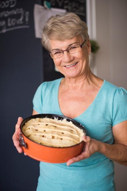 Grootmoeder trots op haar zelfgemaakte cake Gratis Foto