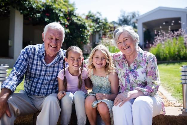 Grootouders en kleindochters die in de tuin zitten Premium Foto