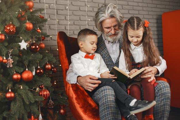 Grootvader draagt een bril, leest een boek voor kleine kleindochters tweeling in een kamer ingericht voor kerstmis. kerst vakantie concept. contrast fotografie Gratis Foto